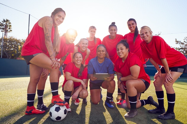 Portrait Of Coach Holding Digital Tablet With Womens Football Team Training For Soccer Match