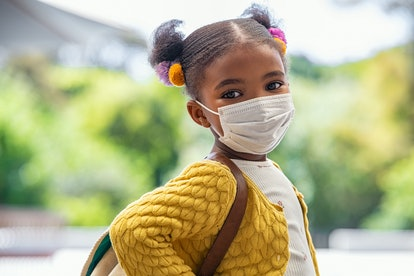 Smiling cute little girl with school backpack and protective face mask ready for first day of school...