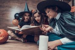 Little Children in Halloween Costumes Reading Book. Cute Smiling Kids wearing Scary Halloween Costum...