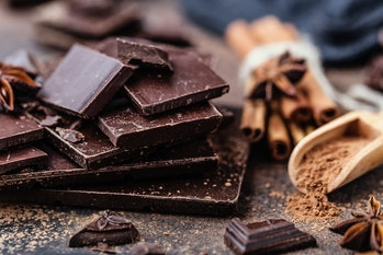 Chocolate bar pieces. Background with chocolate. Sweet food photo concept. The chunks of broken choc...