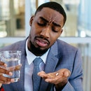 Portrait of a sick young man in business suit taking a medicine pill with water