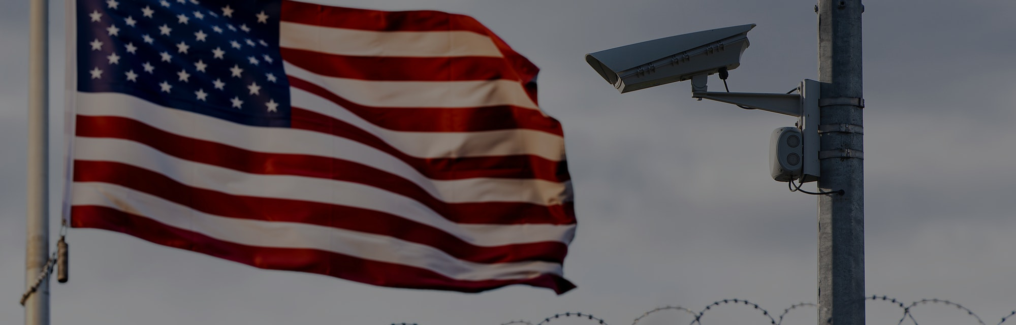 USA border, surveillance camera, barbed wire and USA flag, concept picture