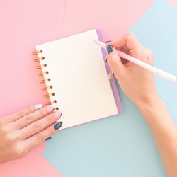 Woman's hands with perfect manicure holding pencil and spiral notepad as mockup for your design. Abstract geometric paper background. Trendy colors pink and blue.