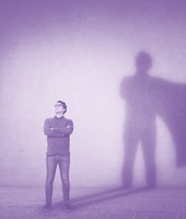 Brave man keeps arms crossed, looks confident, casting a superhero with cape shadow on the wall. Amb...