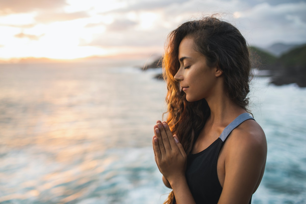 Young woman praying and meditating alone at sunset with beautiful ocean and mountain view. Self-anal...