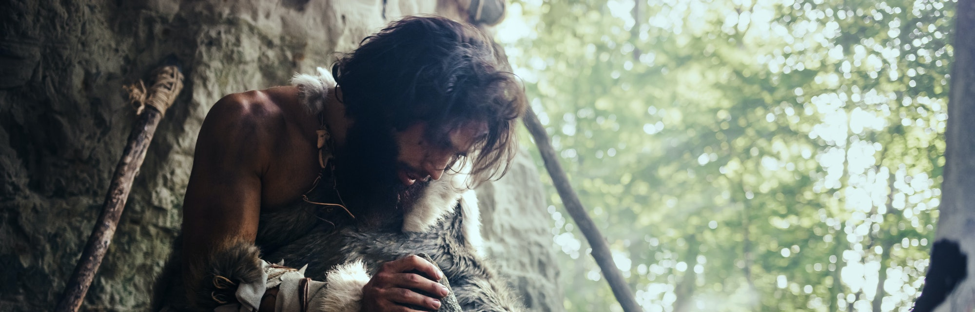 Primeval Caveman Wearing Animal Skin Hits Rock with Sharp Stone and Makes First Primitive Tool for H...