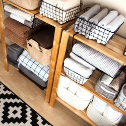 Spring cleaning of closet. Vertical tidying up storage. Neatly folded bed sheets in the metal black baskets for wardrobe. Nordic style.