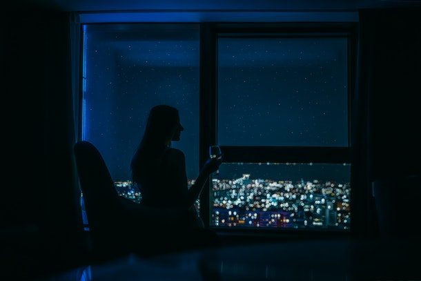 Silhouette of a young woman on the panoramic window background with the glass of vine in her hand and is looking on the night city landscape with stars on the sky.