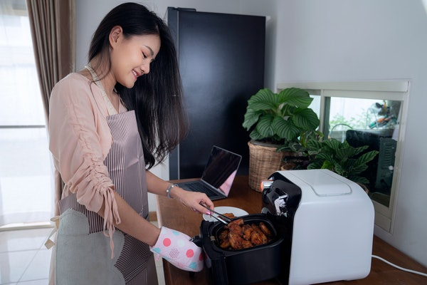 A woman makes wings in her air fryer at home.