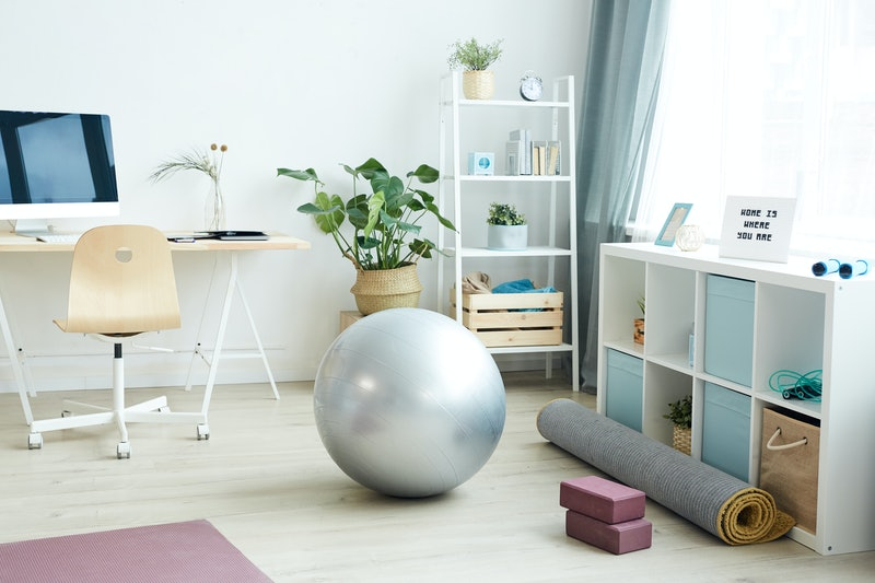 Background image of various sports equipment on floor in small apartment studio, home workout concept, copy space