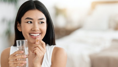 Diet, nutrition, healthy eating concept. Close Up Of Happy Smiling Asian Woman Taking Supplement Pil...