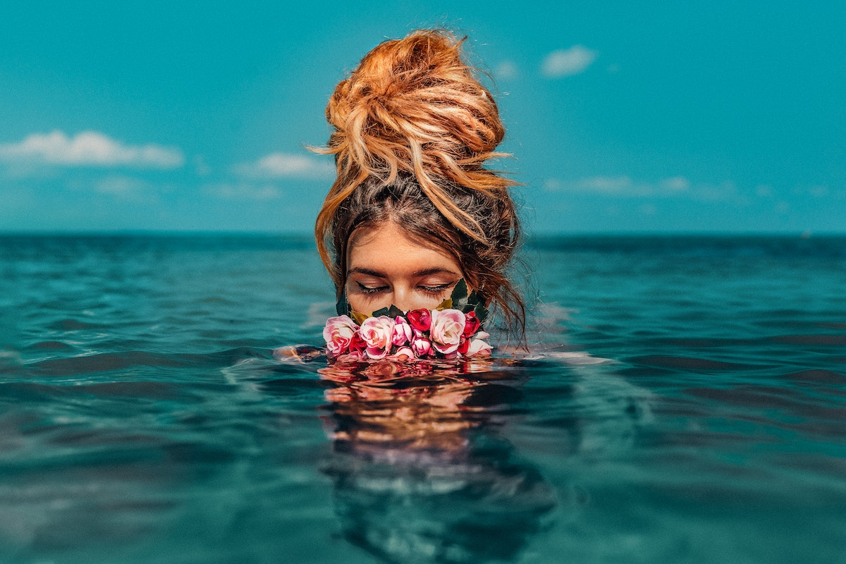 beautiful young woman swimming in sea with wreath conceptual fashion portrait