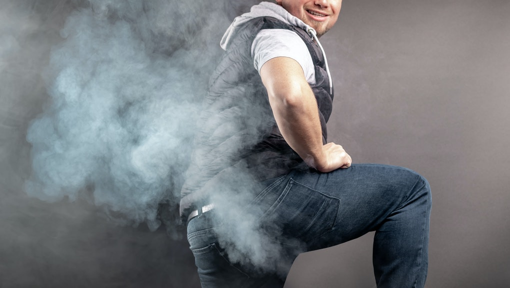 Man lift the leg and fart in front of grey background