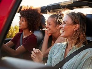 Three female friends on a road trip drive together in an open jeep while on a road trip.