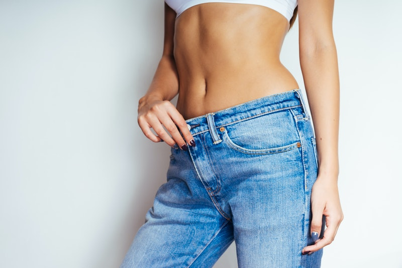 a girl in a white top and blue jeans demonstrates her slender waist and flat stomach