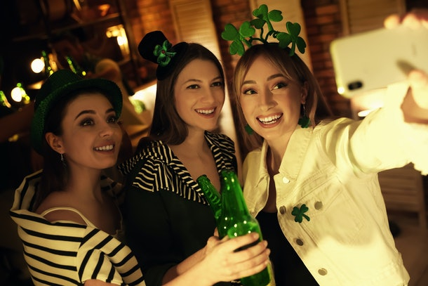 A group of friends pose for a selfie with some beer in a bar on St. Patrick's Day.