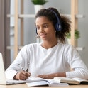 African teen girl wearing headphones study with internet chat skype teacher prepare for exam, black girl school student learning online, watch webinar make notes looking at laptop, distance education