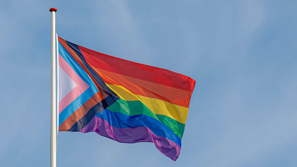 Progress pride flag (new design of rainbow flag) waving in the air with blue clear sky, Celebration ...