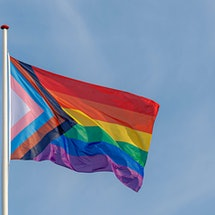 Progress pride flag (new design of rainbow flag) waving in the air with blue clear sky, Celebration of gay pride, The symbol of lesbian, gay, bisexual and transgender, LGBTQ community in Netherlands.
