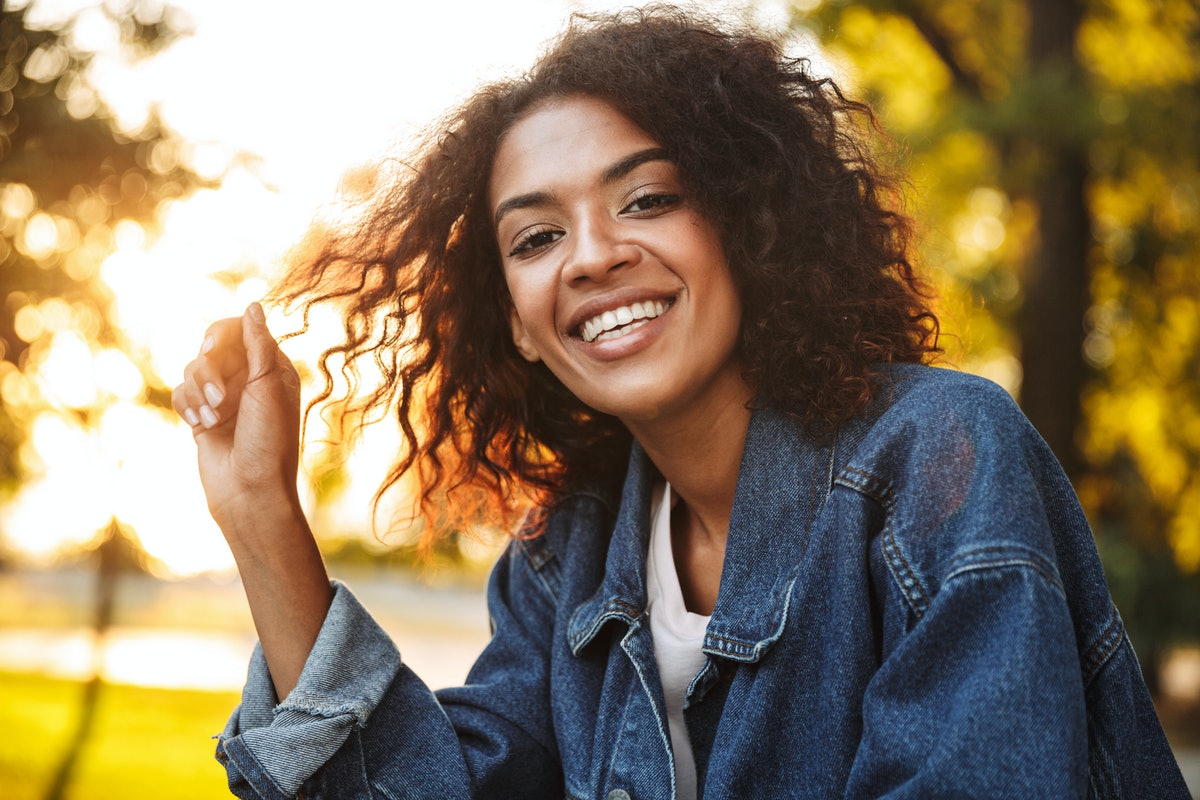 Smiling young african girl in denim jacket spending good time at the park