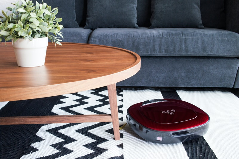 Robotic vacuum cleaner on carpet  in cozy living room with navy blue sofa and wooden table