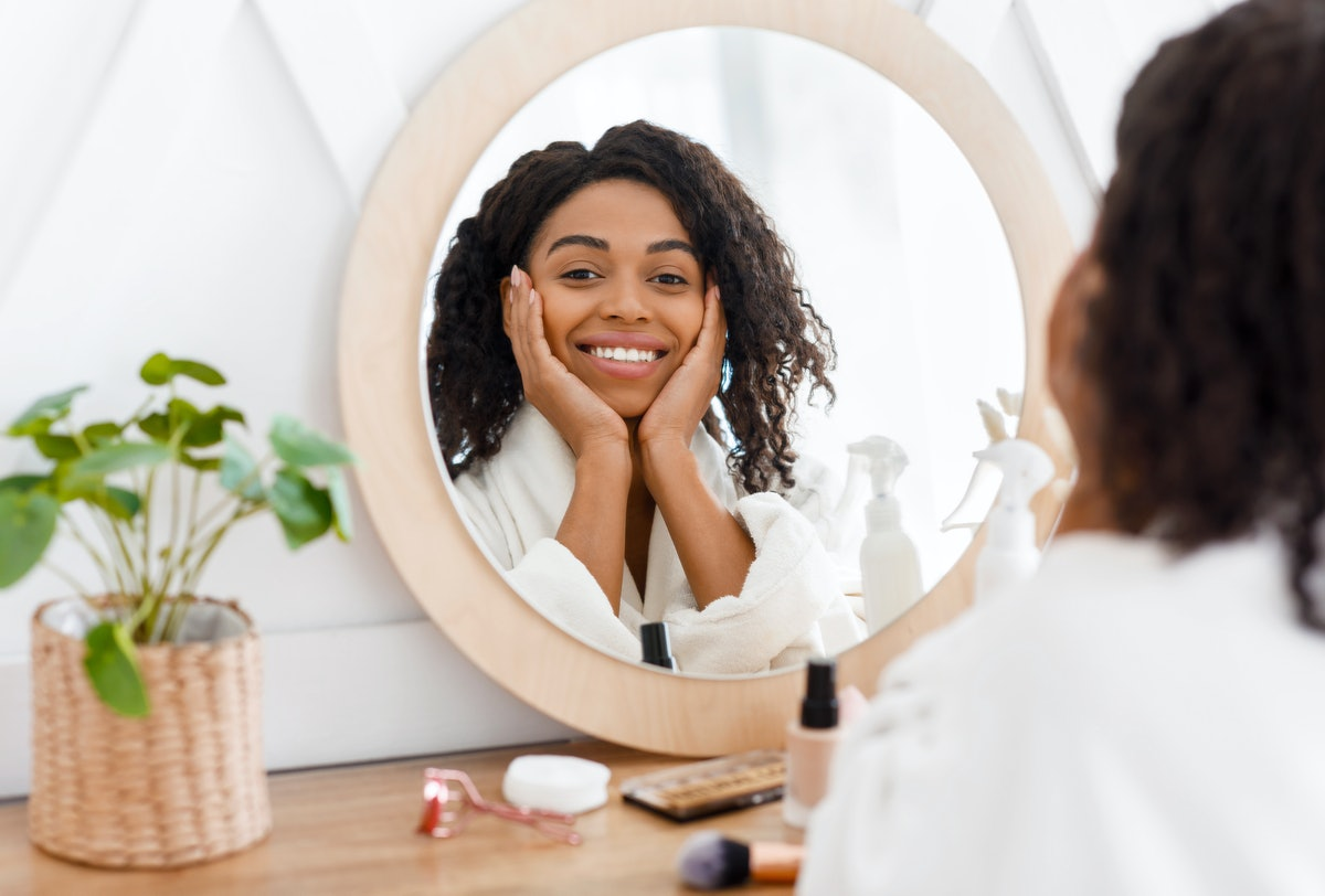 Self-Care. Beautiful African American Woman In Bathrobe Ready To Apply Makeup, Reflecting In Mirror ...