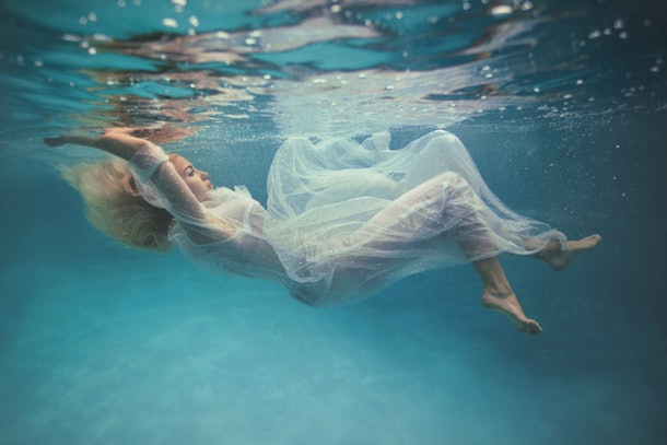 Young blonde woman in vintage white dress swim underwater with orchids flower, floating in Beautiful Mysterious Underwater World. Fantastic and Fairy dreamy fashion. Place for copy text