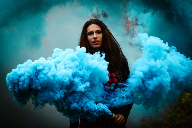 Beautiful girl on a background of colored smoke