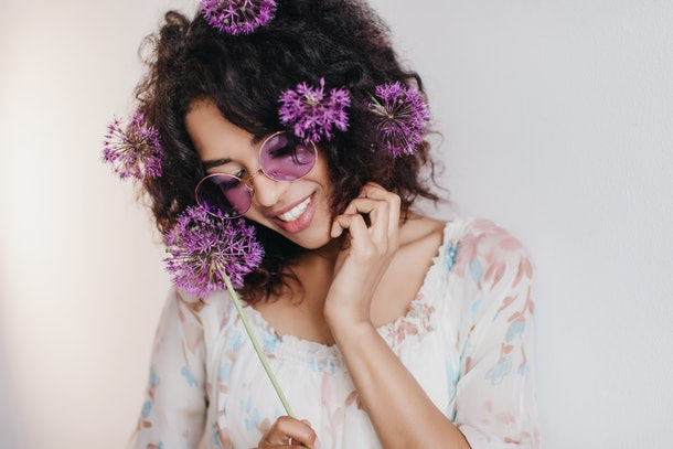 Studio portrait of pleasant african girl dreamy posing on light background. Black young woman with purple flowers in hair smiling during photoshoot.