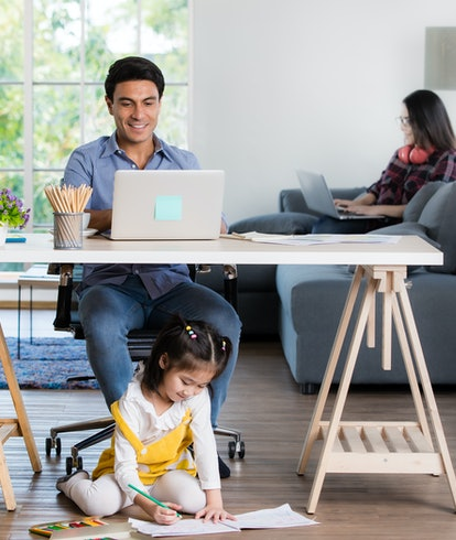 Mixed race family sharing time in living room. Caucasian father using notebook computer to work and half-Thai playing and painting under desk while Asian mother with laptop working her job on sofa.