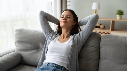 Relaxed serene pretty young woman feel fatigue lounge on comfortable sofa hands behind head rest at home, happy calm lady dream enjoy wellbeing breathing fresh air in cozy home modern living room