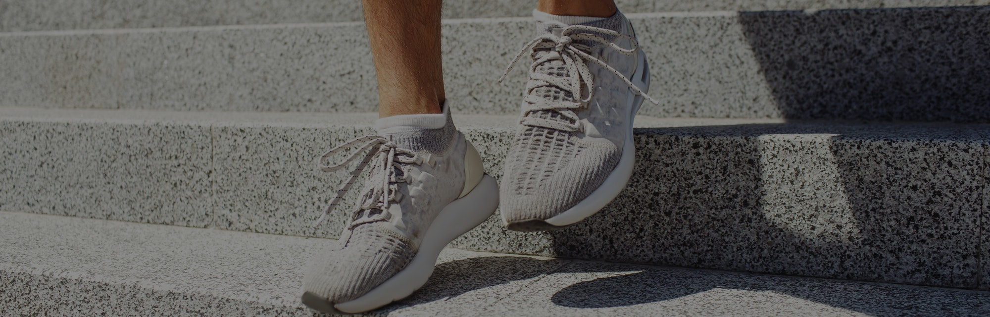 Young man exercising outside. Picture of man's feet in sneakers walking down steps outside duing sun...