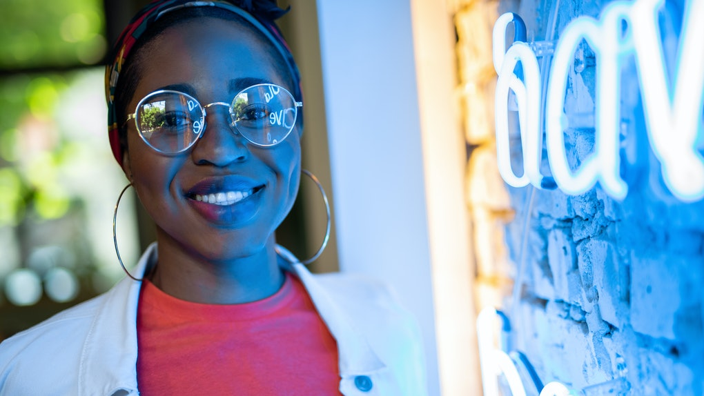 Happy young african american lady standing inside cafe near wall with neon light