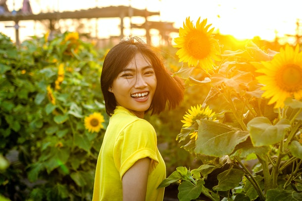 Asian women on the sunflower garden during the summer