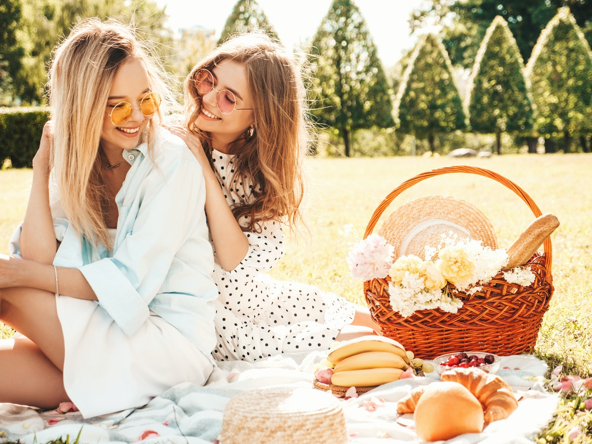 A happy couple enjoys a spring picnic outside with a basket filled with food and gifts.