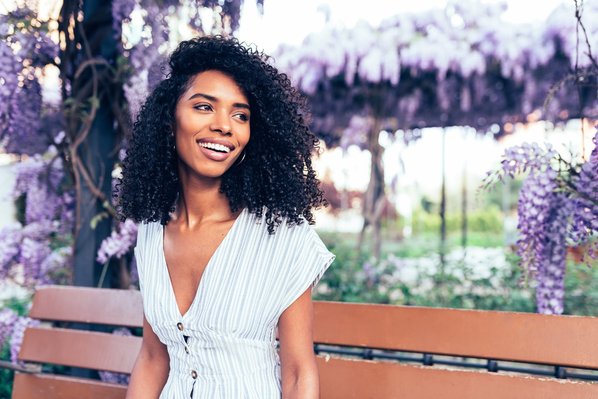 Happy young black woman sitting surrounded by flowers