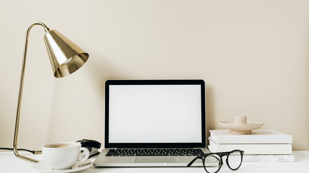 Blank screen laptop. Home office desk table workspace with coffee, lamp, glasses, notebook on beige background. Copy space mockup blog, website template. Blogger, outsourcing freelancer hero header.