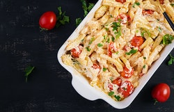 TikTok's viral feta baked pasta recipe made of cherry tomatoes, feta cheese, garlic, and herbs in a casserole dish.