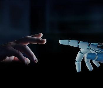 A human finger is seen reaching a robotic finger.