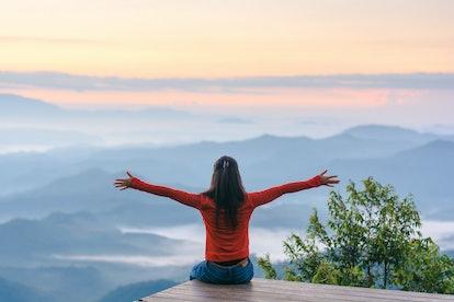 Happy traveler on mountain summit hands raised Travel Lifestyle freedom concept adventure active vac...