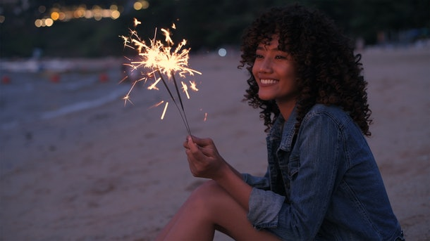 A beautiful woman playing fireworks on the beach.