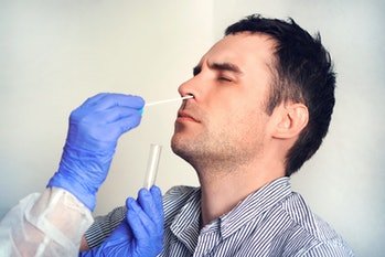 A man is seen undergoing a swab test to detect the contraction of COVID-19.