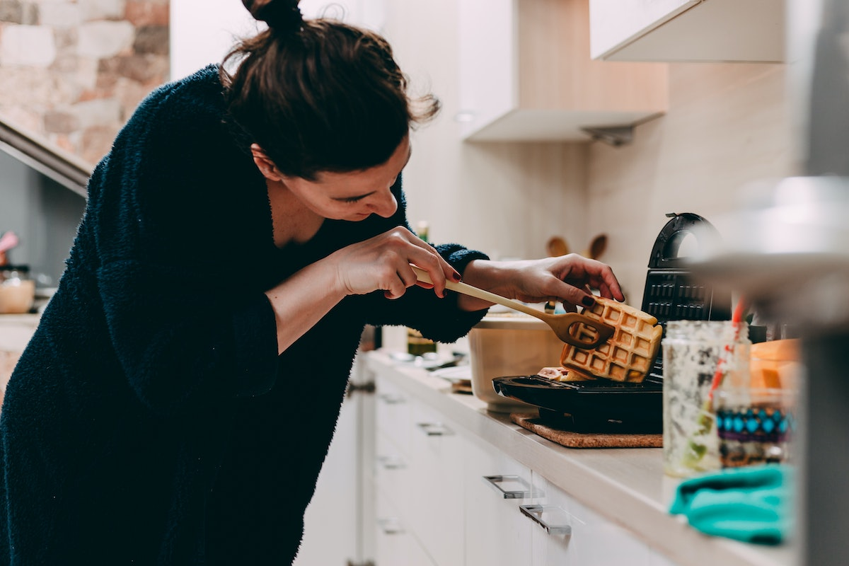 A woman checks out the waffle she's making in her kitchen.