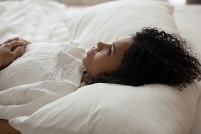 Exhausted African American woman with open eyes lying in bed under white blanket, tired girl with cu...