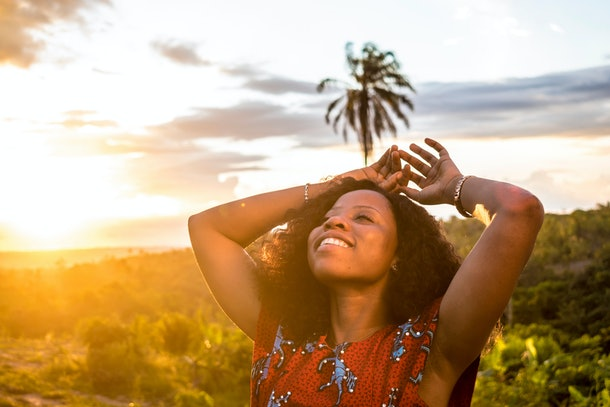 black lady smiling during the beautiful sunset