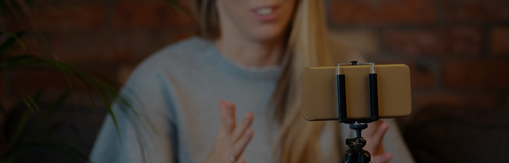 Woman recording video blog at home using mobile phone.