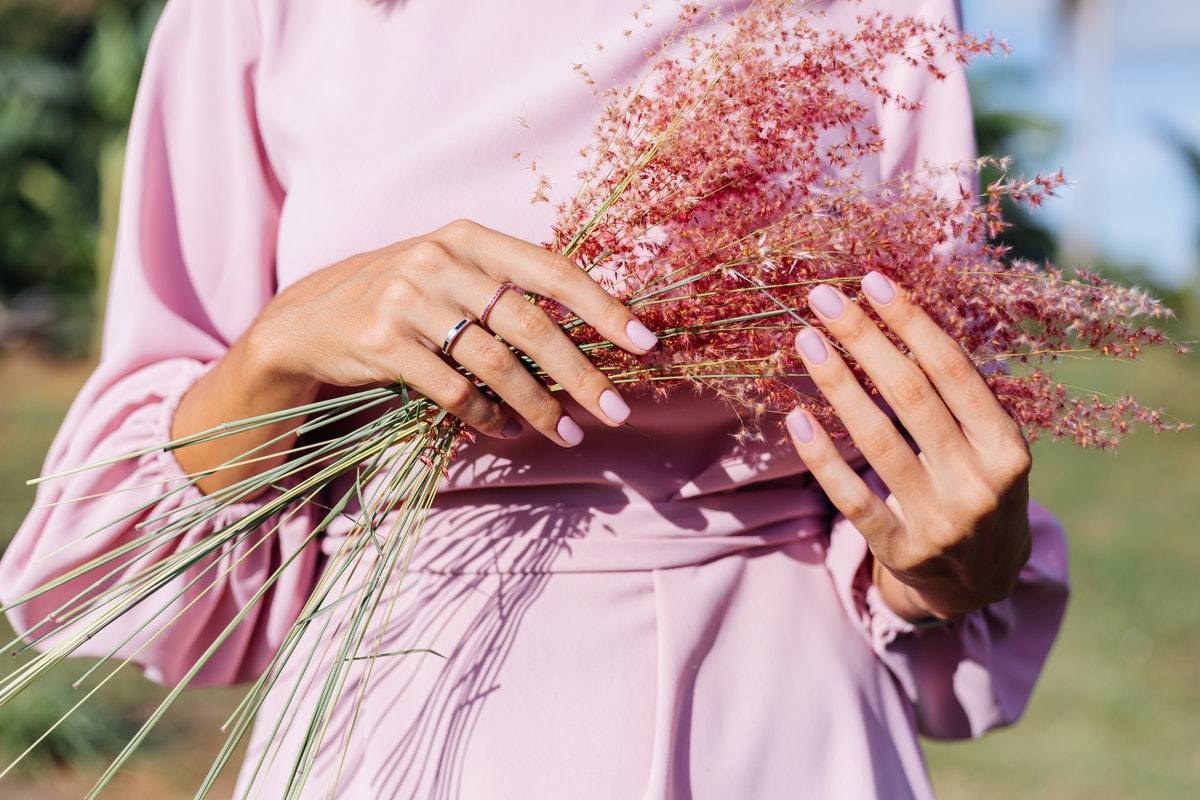Close shot of romantic cute pink gel polished manicure nails. Woman in pink summer dress holding wild flowers. Two rings on fingers. Outdoor portrait.