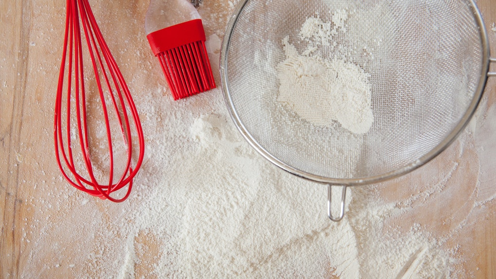 Overhead cooking background. White flour and red silicone tools on wooden cutting board. Baking process copy space.