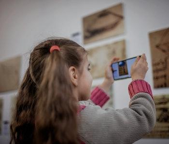 Curious girl exploring a contemporary art exhibition with augmented reality mobile application, futu...
