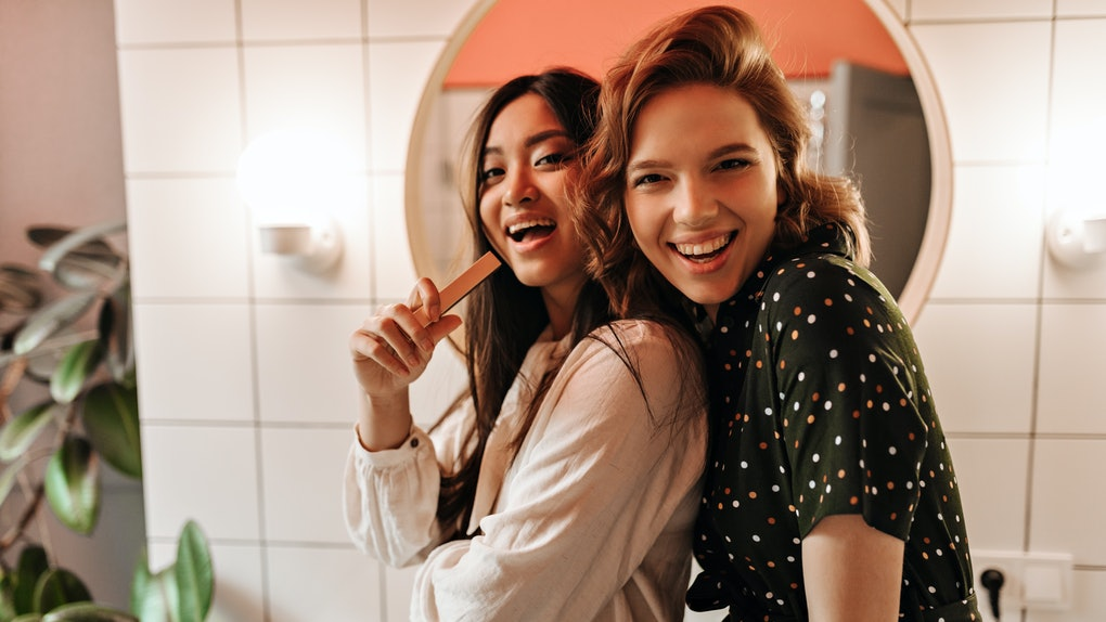 Two friends laugh while hanging out in the bathroom together.